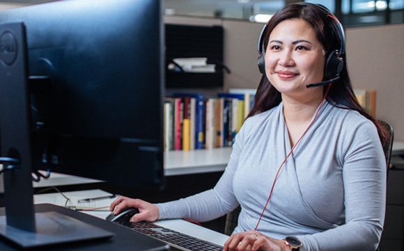 woman working at desk smiling with headset