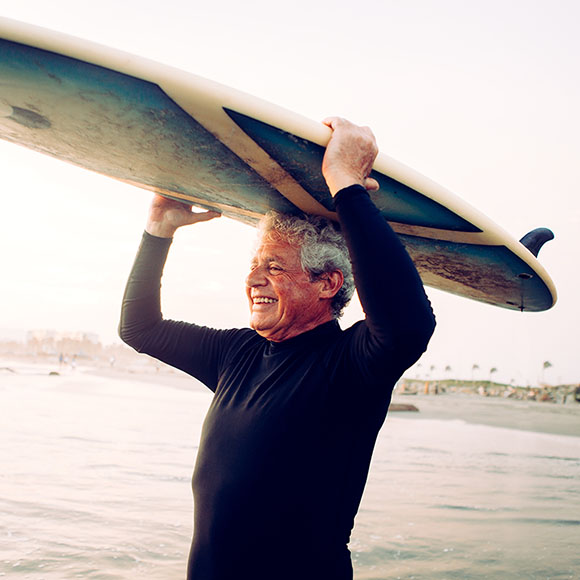 Grandfather enjoying coverage from Medicare supplement plan while surfing