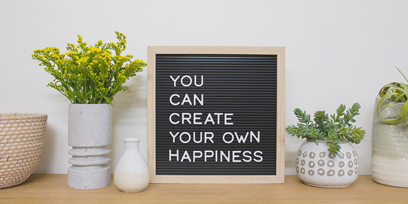 """A small decorative sign that says """"You can create your own happiness"""" sits on a table between two plants and a woven basket."""