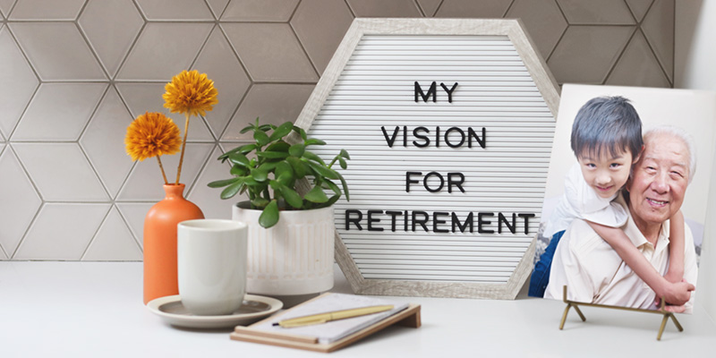 """A small decorative sign that says """"My vision for retirement"""" sits on a table next to two plants, a tea cup, and a notebook and pen."""