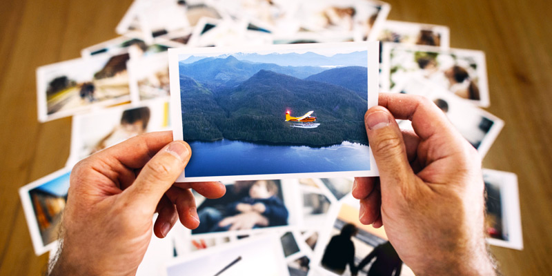A close-up of a man's hands holding an old color photograph of a red seaplane flying over a lake with mountains in the background. Behind the man's hands is a table with a pile of similar photos on it.