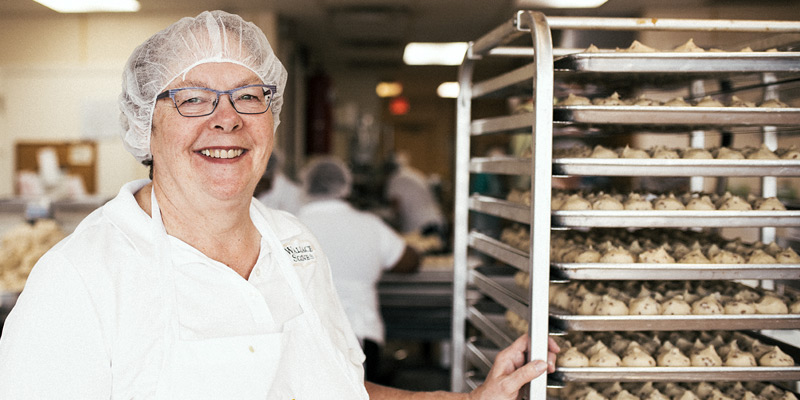Mary Wallace, of Wallace Scones, dressed in a hair net and apron, stands next to a rack filled with trays of unbaked scones. Other workers are in the background
